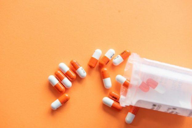 A prescription bottle with medication spilling out.