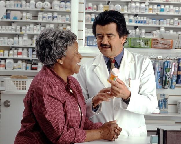 An elderly woman talks to her pharmacist regarding her prescription.