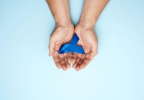 Hands holding dark blue ribbon symbolic of colorectal cancer