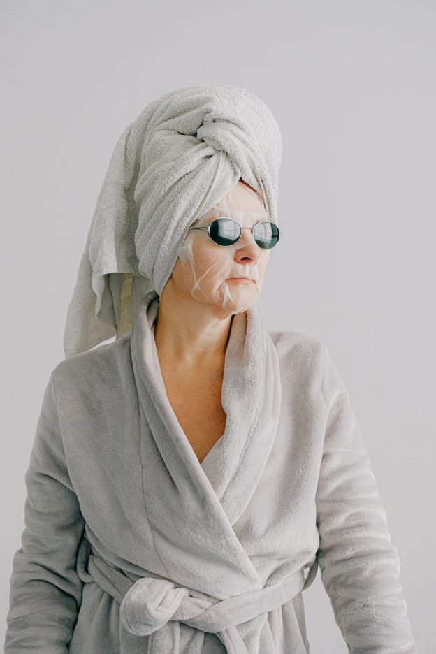 A relaxed woman in bathrobe, towel and face maskA relaxed woman in bathrobe, towel and face mask