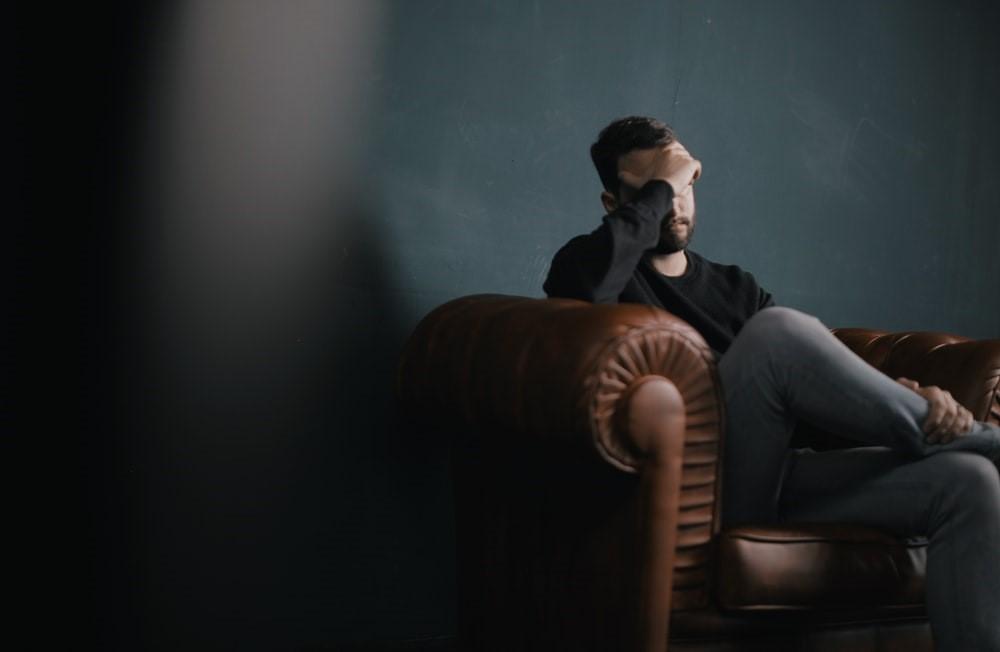 a depressed man sitting
